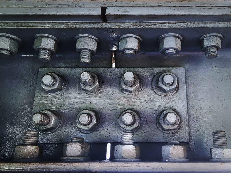 Gray Painted Metal Connecting Plates sammanfogande stålramar med gruppen av bultar och muttrar arkivfoton