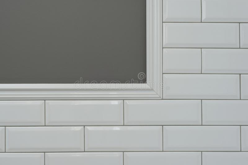 Gray painted wall, part of the wall is covered tiles small white glossy brick, ceramic decorative molding tiles, detail of intrica stock images