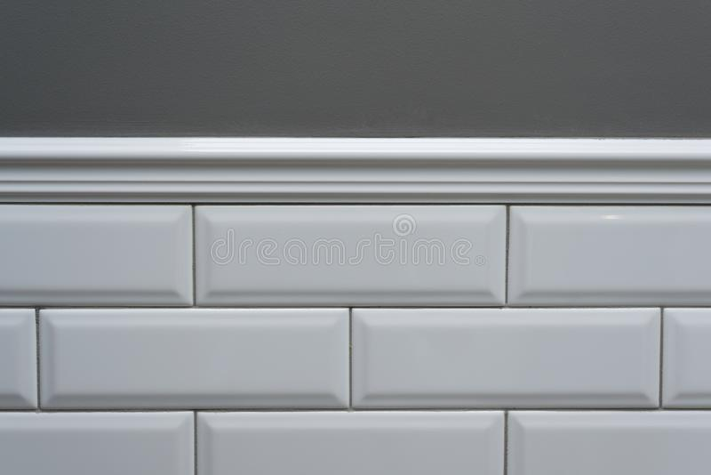 Gray painted wall, part of the wall is covered tiles small white glossy brick, ceramic decorative molding tiles. Fragment of the w stock photos