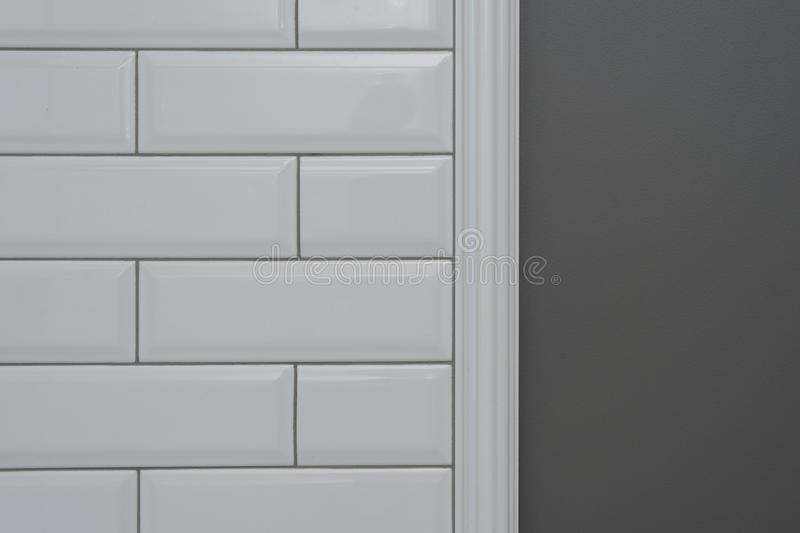 Gray painted wall, part of the wall is covered tiles small white glossy brick, ceramic decorative molding tiles. Fragment of the w royalty free stock photography