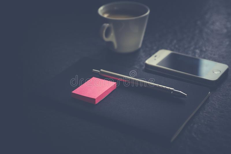 A gray pen and pink sticky notes on a black notebook near white cellphone and coffee mug. A selective shot of a gray pen and pink sticky notes on a black stock images