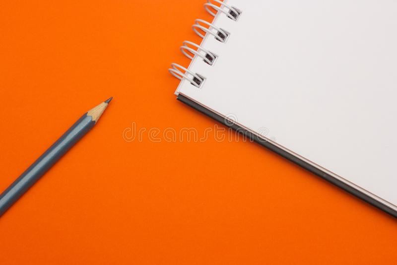 Gray pencil on orange background, back to school, education concept royalty free stock photos