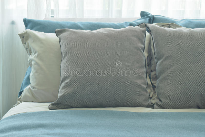 Gray pillows setting on blue color scheme bedding at home. Gray pillows setting on blue color scheme bedding stock photo