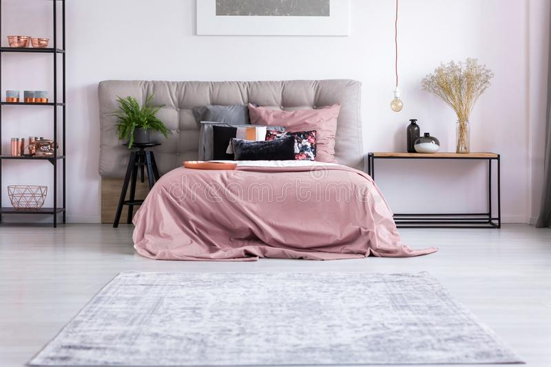 Gray and pink pillowcases. Copper pendant lamp and flowers in vase on wooden nightstand next to king-size bed with gray and pink pillowcases stock photos