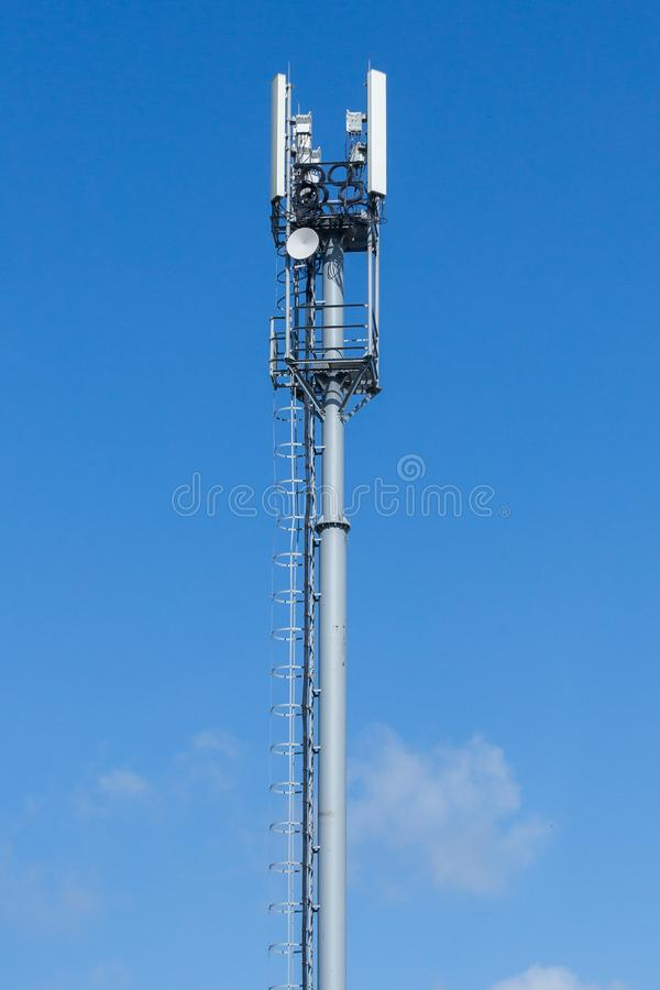 Gray pipe telecommunication tower on blue sky background, Vertical shot royalty free stock photo