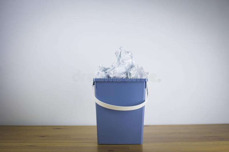 Gray trash bin filled with crumpled paper royalty free stock photo