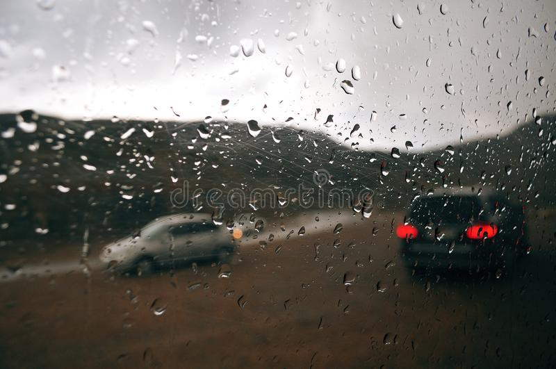 Gray raindrops on the car window on a cloudy day. Outside the window of the car silhouettes of passing cars royalty free stock photography