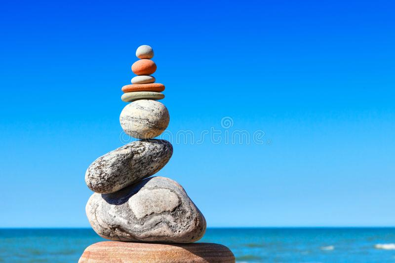 Gray and red zen stones on the background of the sea. Concept of harmony, balance and meditation.  royalty free stock images