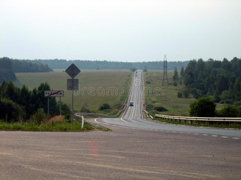 A gray ribbon of road between fields and forests on a cloudy day royalty free stock photography