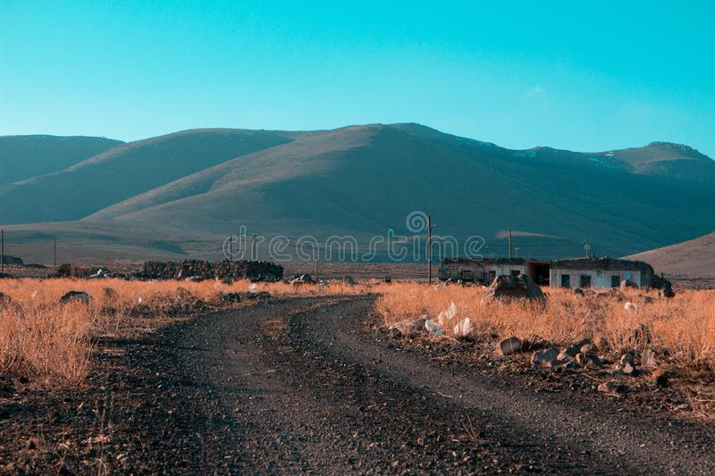 Gray Road in Between Brown Grass Field With Mountains Background stock images