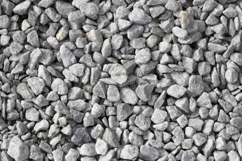 Gray Rock Background. Gray white stones that act as gravel for drainage in flowerbeds and plantings in a wide variety of landscape areas royalty free stock photography