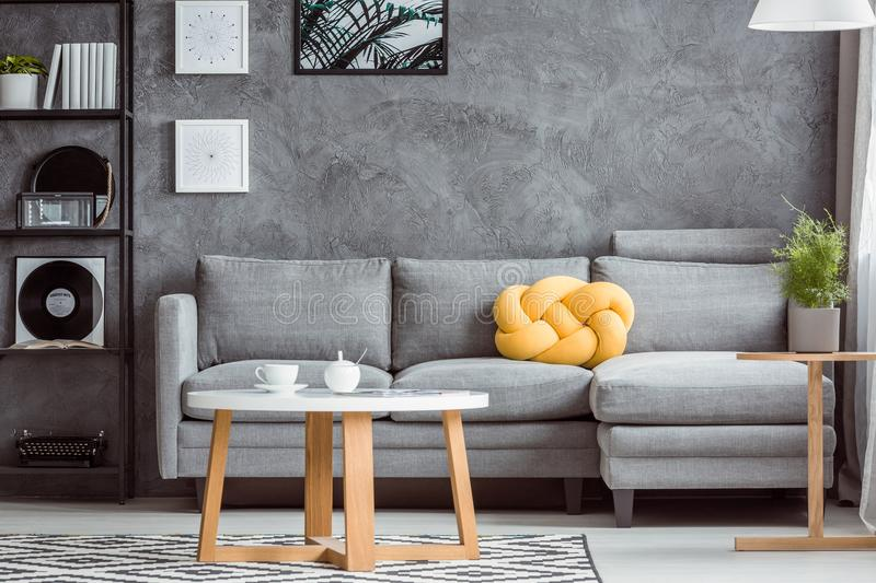 Gray room with yellow accent. Close-up photo, contemporary design of cozy gray living room interior with simple sofa and yellow accent royalty free stock image
