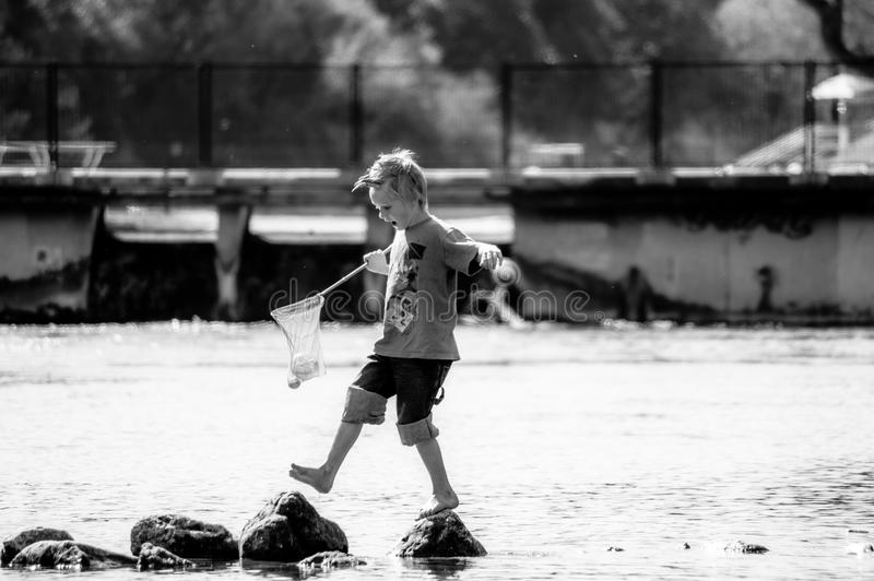 Gray Scale Photo Of Boy On Top Of Stone On Body Of Water Holding Fishing Net During Daytime Free Public Domain Cc0 Image