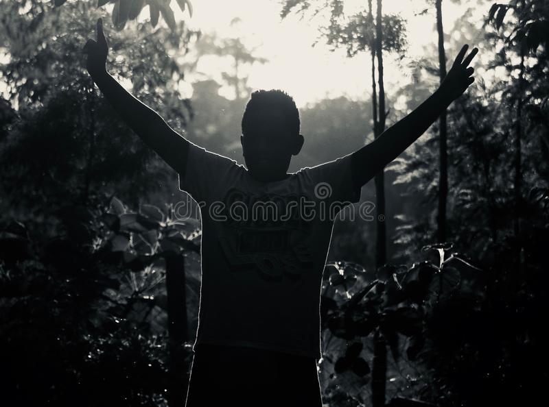 Gray Scale Photo of Man in White Shirt Raising His Hand Near Plants stock image