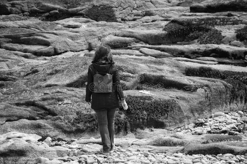 Gray Scale Woman in Black Hoodie Jacket on Concrete Rock stock images