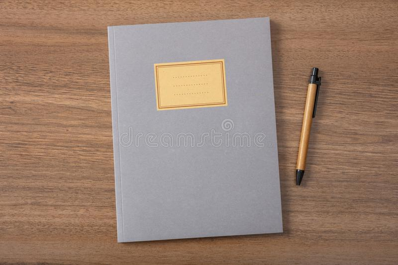 Grey school notebook or diary, old fashioned, on wooden desk, blank label, space for text, top view. Gray school notebook or diary, old fashioned, and pen on royalty free stock images