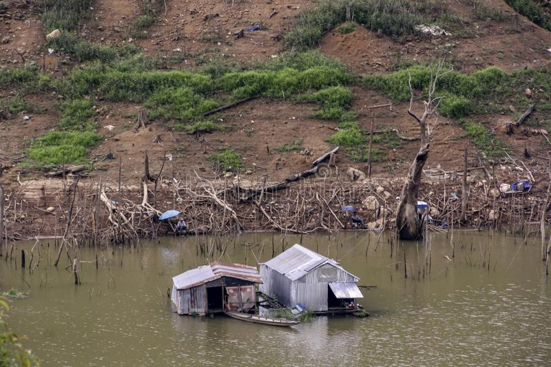 Gray shack house built of tin sheets on the river stock photography