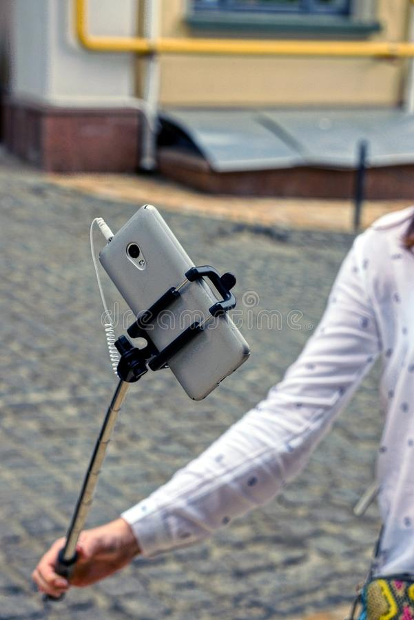 Gray smartphone on monopod in girl`s hand. A girl is holding a gray smartphone on a stick royalty free stock images