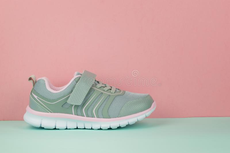 Gray sneaker on the right foot on a blue and pink background. Sports shoes royalty free stock photos
