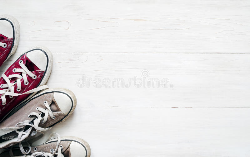 Gray sneakers and claret sneakers on white wooden floor background. Top view stock photography