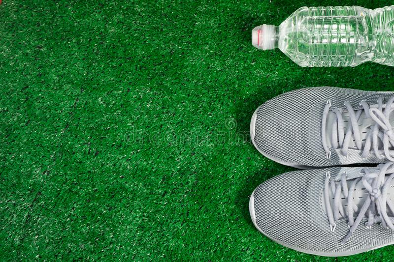 Gray Sports Running Shoes and bottle of water on green grass. stock image