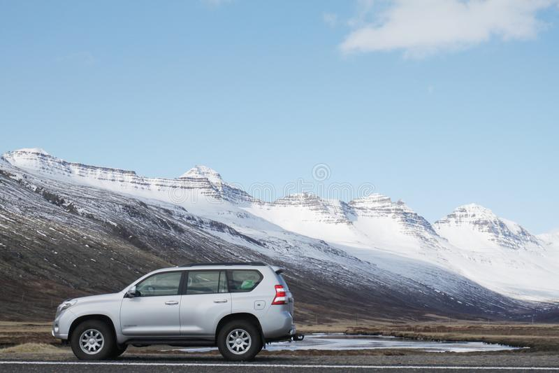 Gray Sports Utility Vehicle on Road Near Snow Covered Mountain stock photo