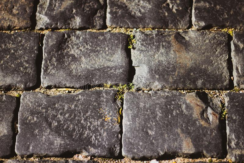 Gray square cobblestones close-up. The stone surface of the road. The road of stones and cobblestones royalty free stock photography
