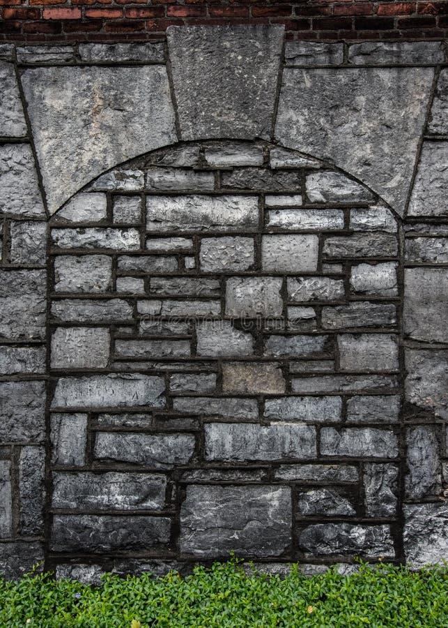 Gray Stone Arch med röd tegelsten och gräsplanmurgrönan arkivfoto