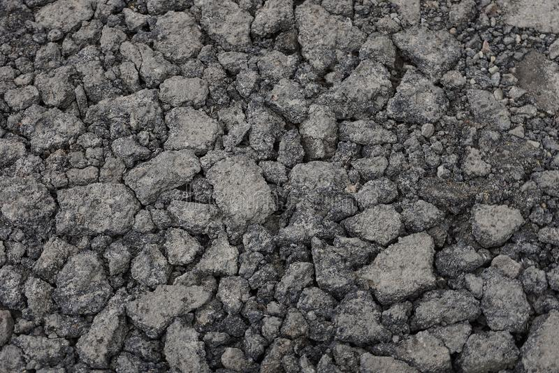 Gray stone texture of asphalt pieces with cracks on the road. Gray stone background of pieces of asphalt with cracks on the road stock photo