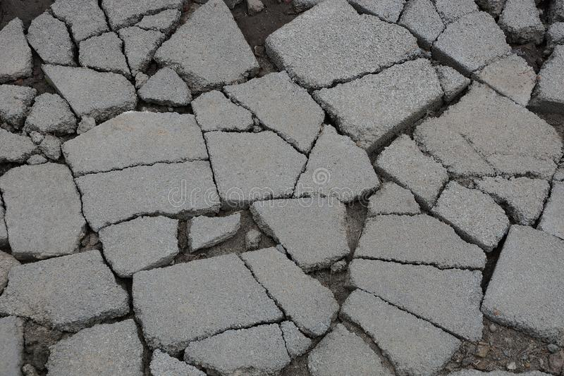 Gray stone texture of asphalt pieces with cracks on the road. Gray stone background of pieces of asphalt with cracks on the road royalty free stock photo