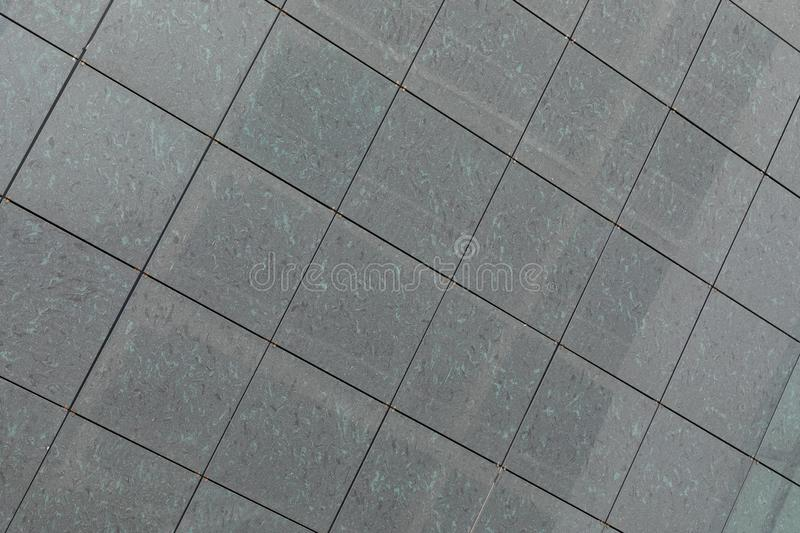 Gray stone square tiles on wall or floor, ground with diagonal view. stock images