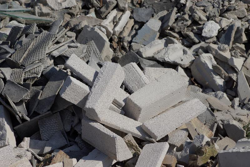 Gray stone background of pieces of bricks and concrete in a pile of garbage on the street. Gray stone texture of pieces of bricks and concrete in a pile of stock images