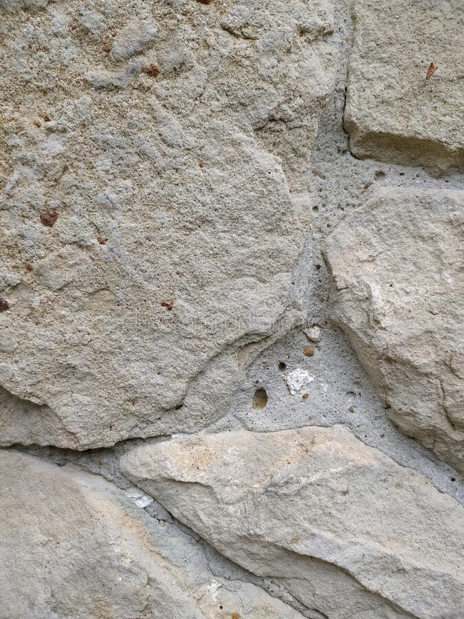 Gray stone wall background, mosaic stonewall rubble facade closeup texture stock images