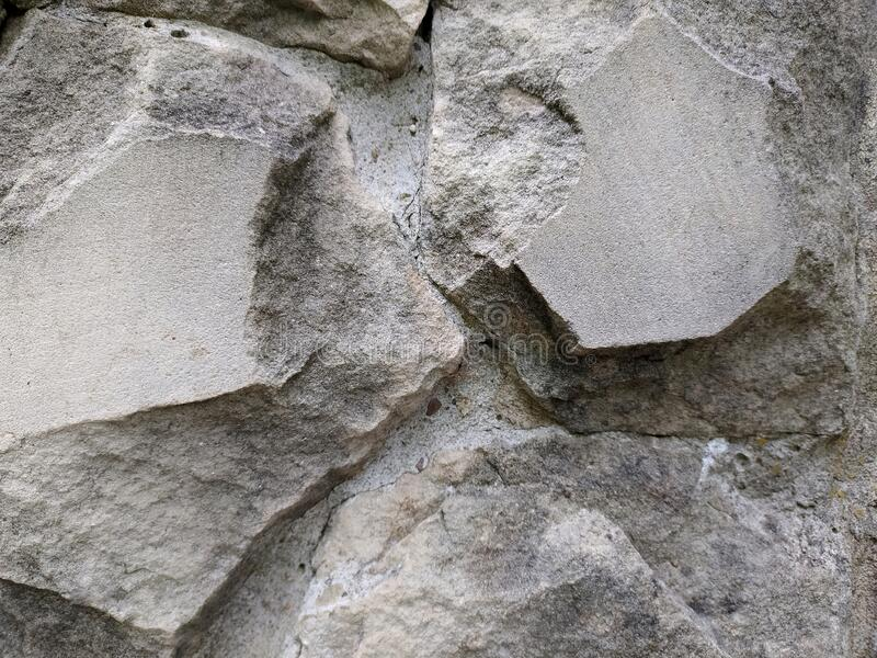 Gray stone wall background, mosaic stonewall rubble facade closeup texture stock photo