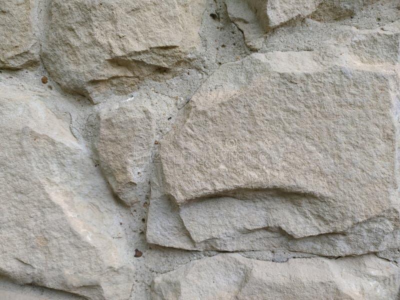 Gray stone wall background, mosaic stonewall rubble facade closeup texture stock photos