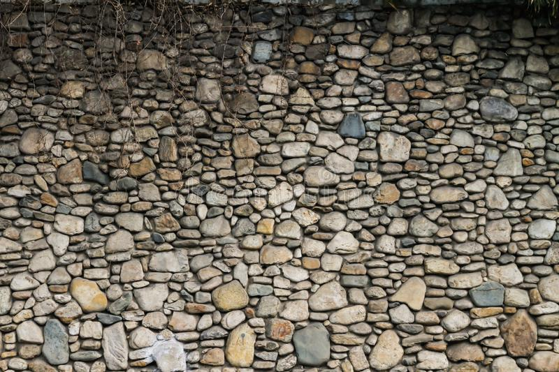 Gray stone walls with beautiful patterns with ivy on top royalty free stock images