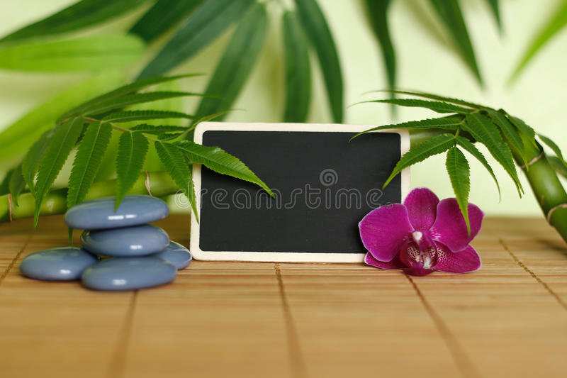 Gray stones arranged in Zen lifestyle with an orchid, a lighted candle, a bamboo branch and foliage and an empty message slate. Stones arranged in Zen lifestyle stock image