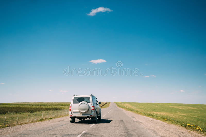 Gray SUV Car rides along Road In Spring Summer Fields Landscape. Drive And Travel Concept royalty free stock images