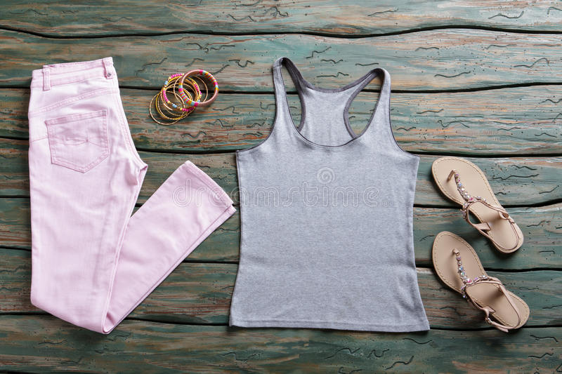 Gray tank top and pants. Light pink trousers and footwear. Summer outfit with simple top. Discounted goods in brand store royalty free stock photo