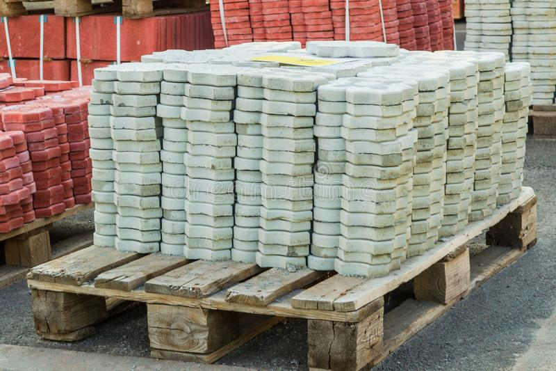 Tiles piled in pallets, warehouse paving slabs in the factory for its production. Gray tiles piled in pallets, warehouse paving slabs in the factory for its stock photos