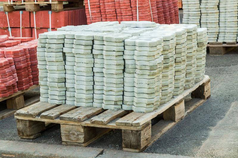 Tiles piled in pallets warehouse paving slabs the factory for its production. Gray tiles piled in pallets warehouse paving slabs the factory for its production stock images