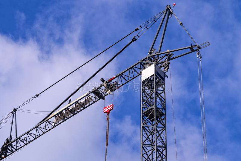 Gray tower crane against the cloudy blue sky stock photo