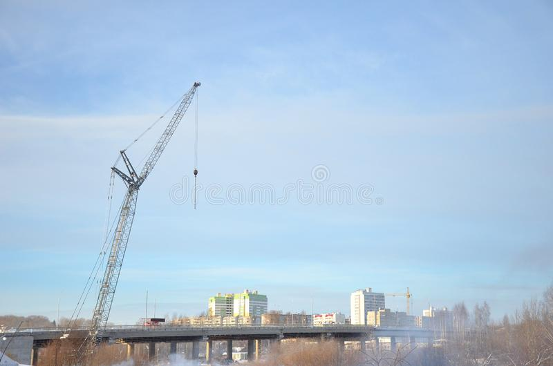 Gray tower crane towering over the bridge on the background of high-rise buildings and blue sky royalty free stock photography