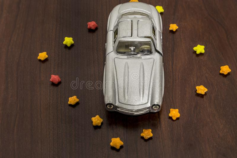 Gray toy car in colorful sugar stars on wooden background.  stock image