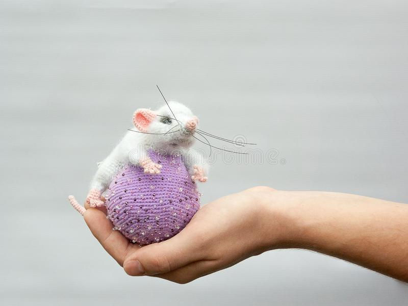 Gray toy mouse on a lilac ball, symbol of the new year royalty free stock photo