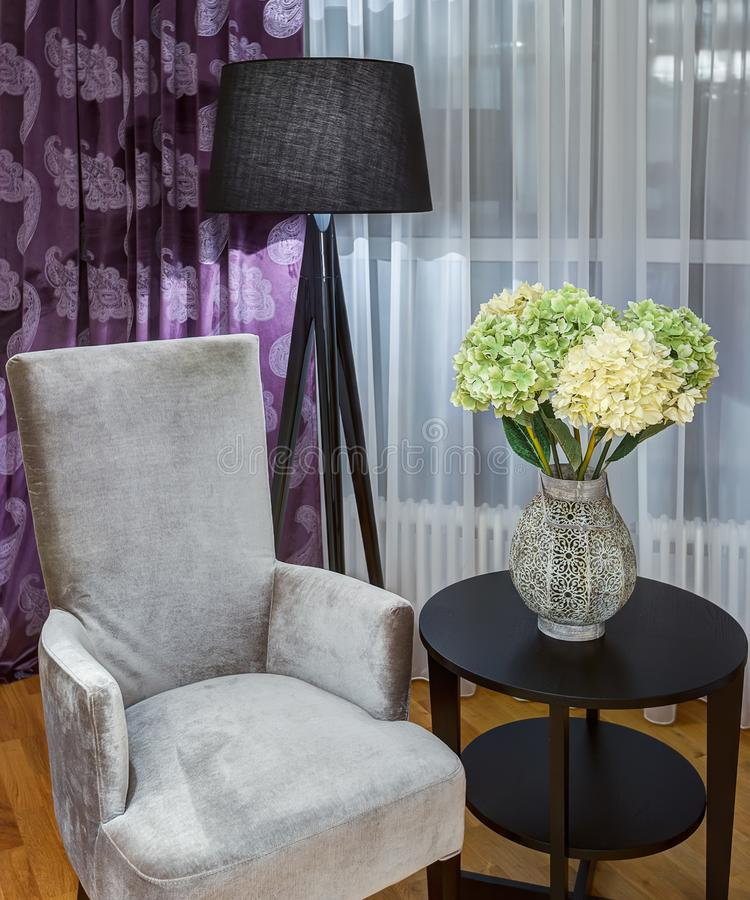 Gray velor armchair near rounded table. royalty free stock image