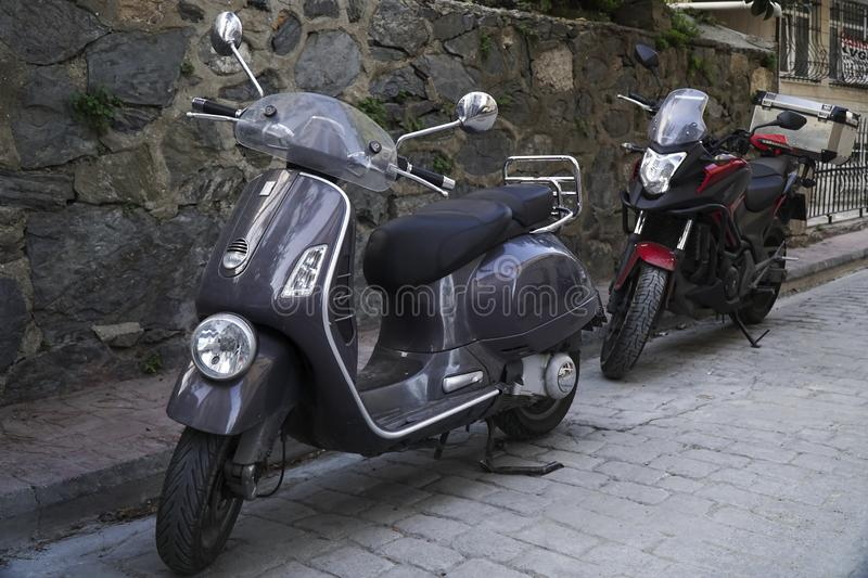Gray vintage Vespa and a red and black colored Honda Touring Motorcycle stock photos