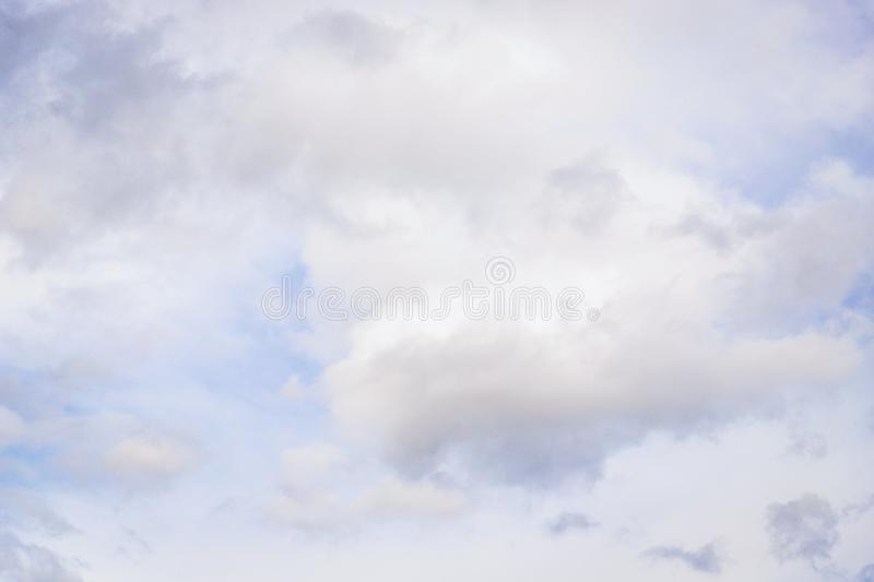 Gray white fluffy clouds on light blue sky background royalty free stock photography