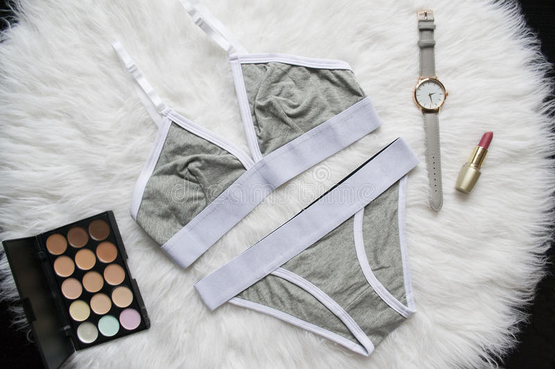 Gray white linen set for sports on a white fur. Watches, lipstick, eye shadow. Fashionable concept. Top view stock images