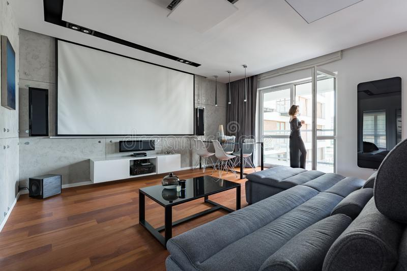 Gray and white living room. With sofa, table, balcony and projector screen stock photo